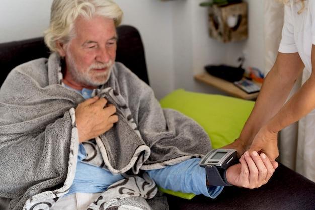 Oude senior man thuis met een slecht gezondheidsprobleem zittend op de bank terwijl de vrouwelijke arts de bloeddruk controleert met moderne tool