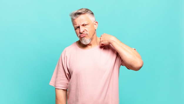 Oude senior man voelt zich gestrest, angstig, moe en gefrustreerd, trekt aan de nek van het shirt, ziet er gefrustreerd uit met een probleem