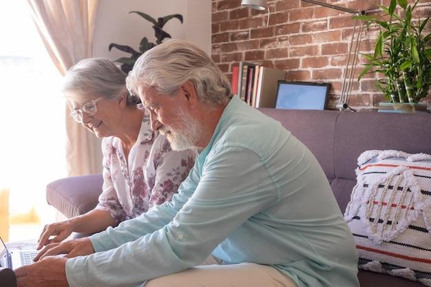 Oude senior paar zittend op de bank thuis met behulp van dezelfde laptopcomputer. ouderen genieten van technologie en sociale media. bakstenen muur op achtergrond