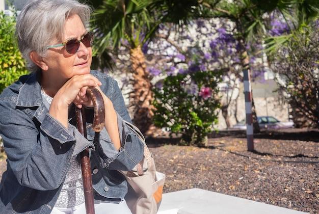 Oude senior vrouw met handen over het riet zitten in openbaar park met droevige uitdrukking. oudere gepensioneerde met rugpijn met behulp van wandelstok. boom en bloemen op achtergrond