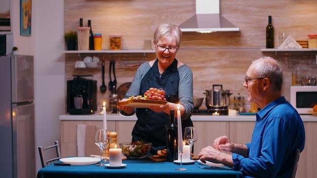 Oude senior vrouw serveert haar man met druiven en kaas. bejaard oud echtpaar praten, aan tafel zitten in de keuken, genieten van de maaltijd, hun jubileum thuis vieren met gezond eten.
