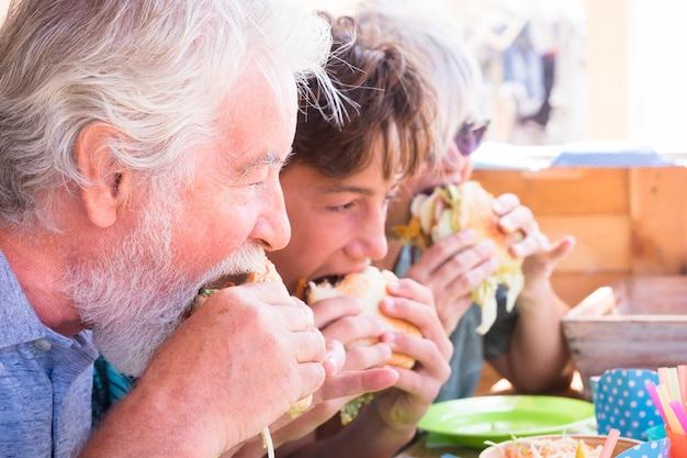 Oude senioren en jonge tienerfamilie die allemaal samen hamburger eten - grootvaders met kleinzoon vriendschapsconcept - blanke mooie volwassene en jong eten thuis of fastfood