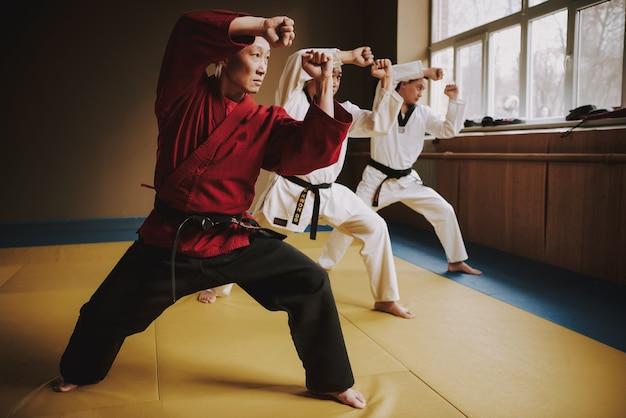 Oude sensei en twee vechtsportenstudenten die samen trainen.