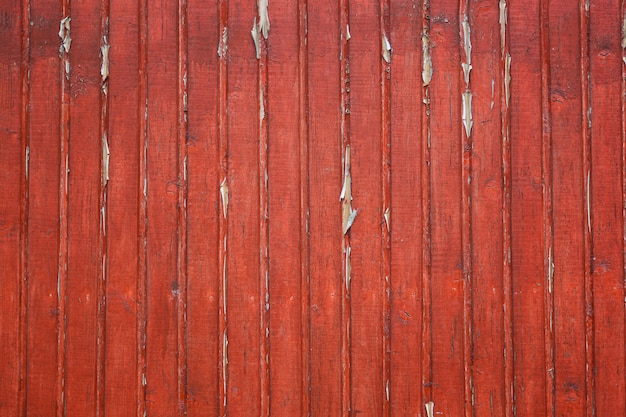 Oude sjofele houten planken met rode gebarsten kleur verf als achtergrond.