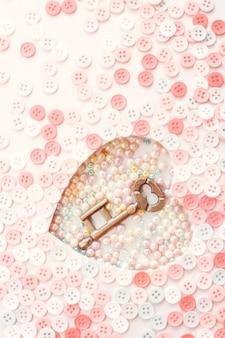 Oude sleutel met decoratieve buttons.valentijnsdag concept achtergrond.