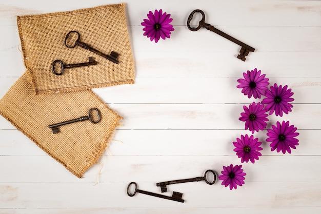 Oude sleutels met bloemen op houten achtergrond