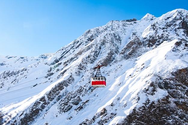 Oude slinger kabelmanier bij bergen landschap en blauwe hemelachtergrond op winterdag in skigebied