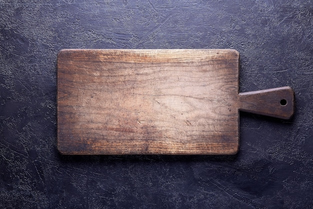 Oude snijplank op donkere betonnen achtergrond, kopieer ruimte voor uw tekst