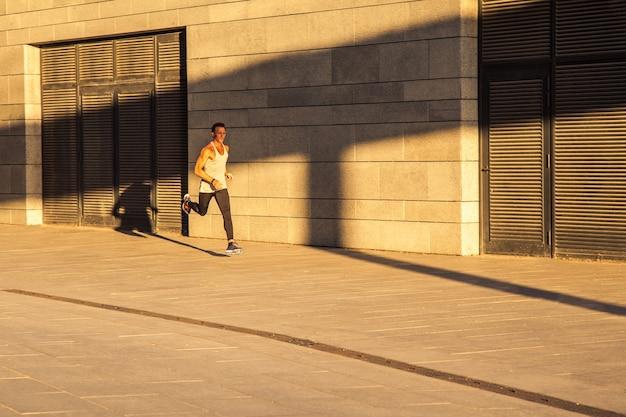 Oude sportman die op landweg loopt