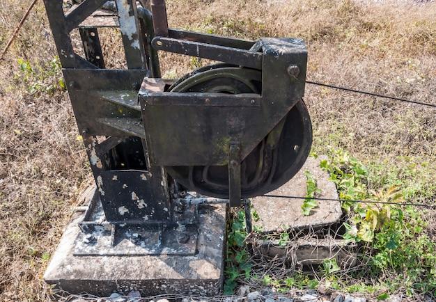 Oude staalkatrol met de metaaldraad van de verkeerslichtpool.
