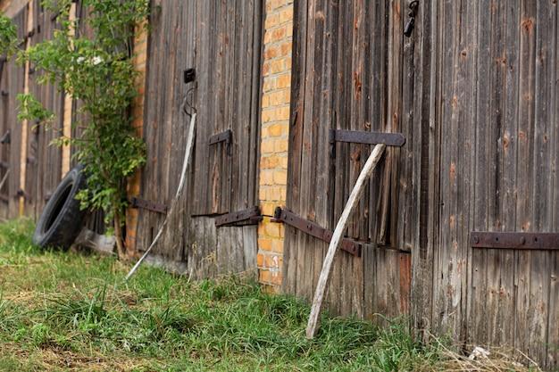 Oude stal. grote houten poort en gedroogd hout. oude bakstenen gebouw