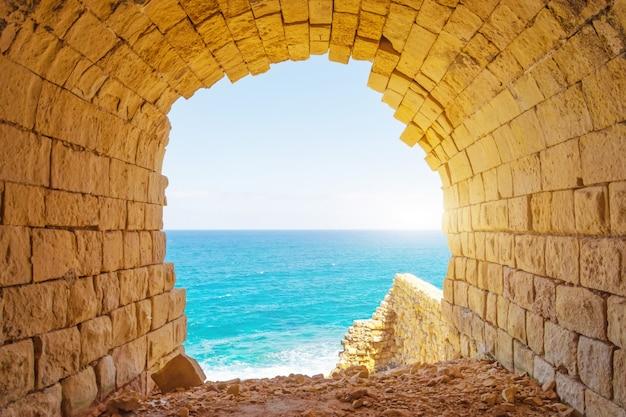 Oude stenen boog met uitzicht op de blauwe tropische zee.