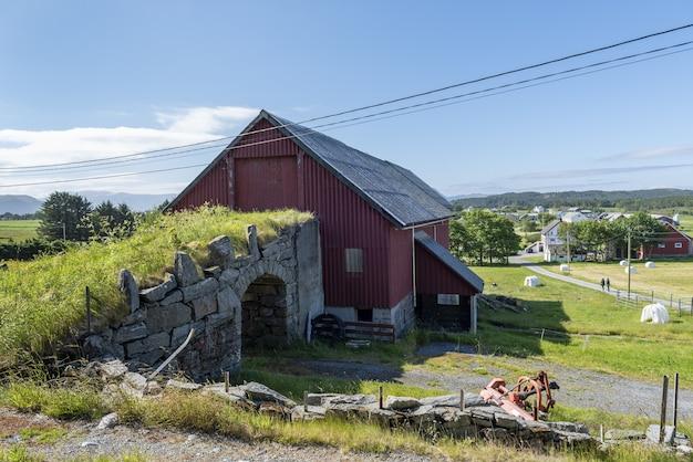Oude stenen brug die verbinding maakt met een rode schuur, omringd door groen en korte bomen in alesund, noorwegen