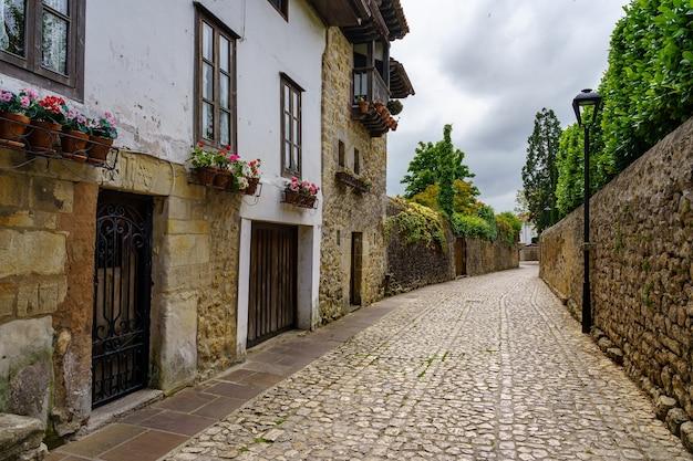 Oude stenen dorpsstraat met muren bedekt met groen en bloemen. santillana del mar, cantabrië