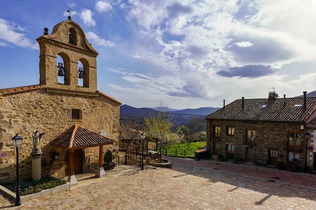 Oude stenen kerk in middeleeuws dorp met oude huizen en blauwe hemel met wolken