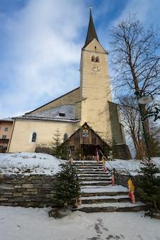 Oude stenen kerk met hoge klokkentoren in oostenrijkse alpen