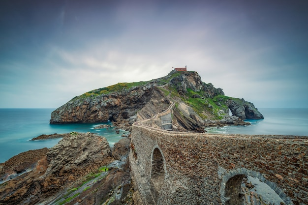 Oude stenen muur gaat over de oceaan naar een eiland