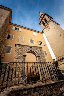 Oude stenen poorten en hoge toren op straat van budva, montenegro