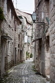 Oude stenen smalle straatjes van trogir, kroatië. verticale opname