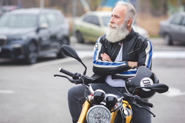 Oude stijlvolle man die de motorfiets bestuurt