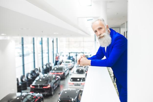 Oude stijlvolle man in autoverkoopcentrum