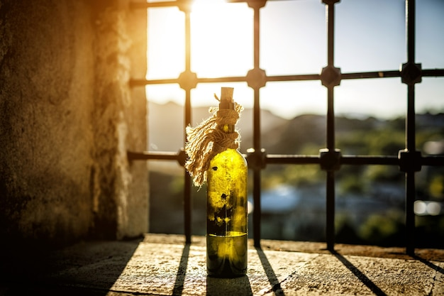 Oude, stoffige fles wijn op de vensterbank