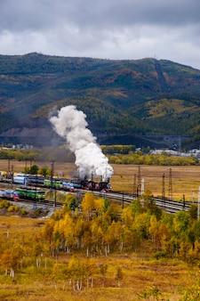 Oude stoomlocomotief in de circum-baikal railway met rook in de herfst
