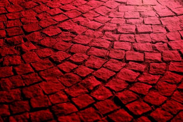 Oude straatstenen bij nacht in rood licht
