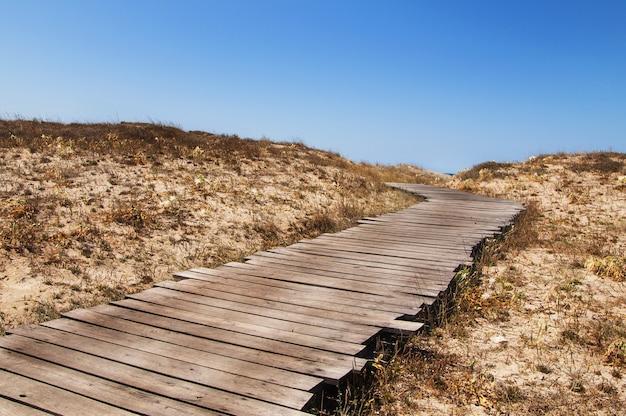 Oude strand houten loopbrug op het toneel van de heldere blauwe lucht