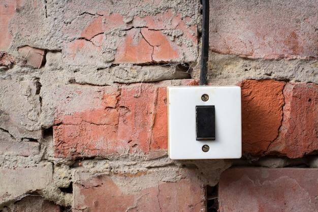 Oude switcher op de bakstenen muur met draad