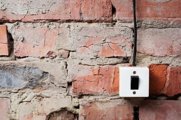 Oude switcher op de bakstenen muur met draadachtergrond