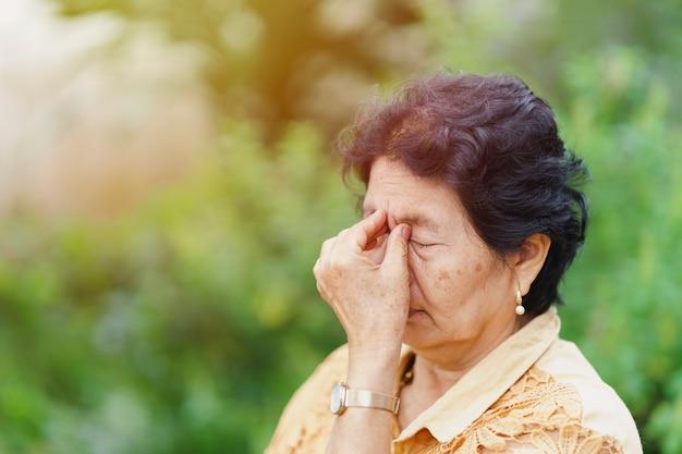 Oude thaise vrouw masseert de oogkas vanwege oogpijn. gezondheidszorgconcept.