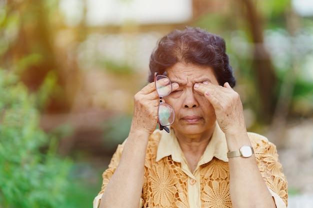 Oude thaise vrouw masseert oogkassen vanwege oogpijn na te veel ogen te hebben gebruikt