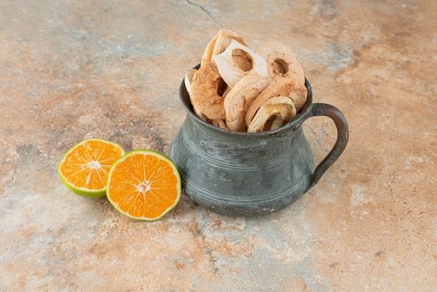 Oude theepot vol gedroogde appels met half gesneden mandarijn