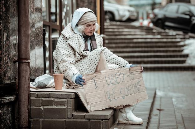 Oude tijden. droevige bejaarde vrouw die aan haar vorige leven denkt terwijl ze op straat zit