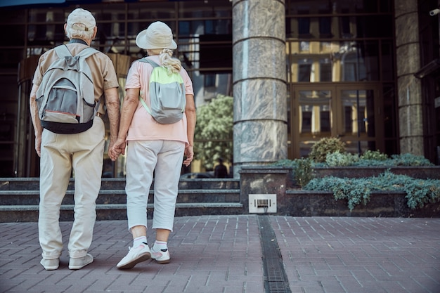 Oude toeristen met rugzakken die voor een modern kantoorgebouw staan