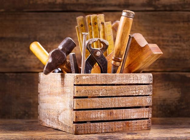 Oude tools in een houten kist op houten achtergrond