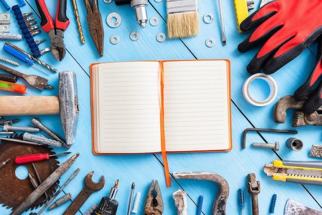 Oude tools op het bureaublad met kladblok.