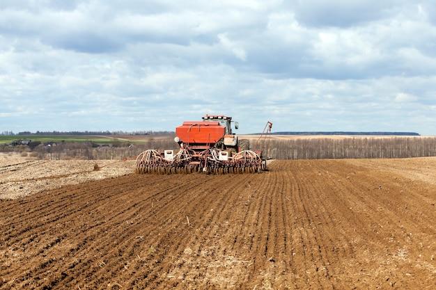 Oude tractor die tarwe in de lente opbrengt.