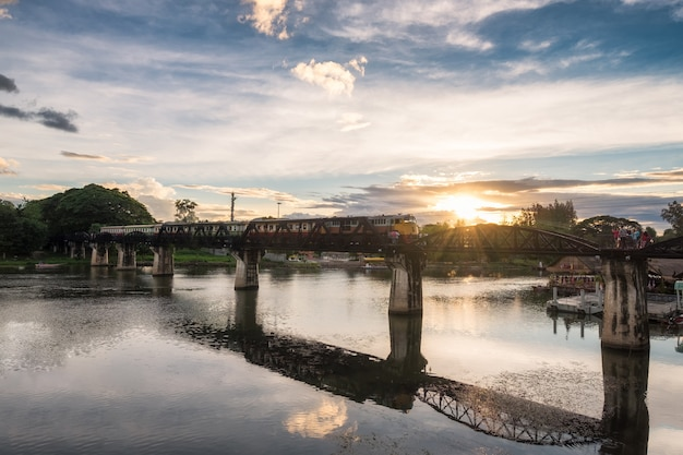 Oude trein die op brug in het oriëntatiepunt van rivierkwai van kanchanaburi loopt