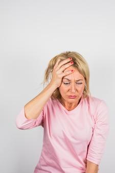 Oude trieste vrouw in roze blouse