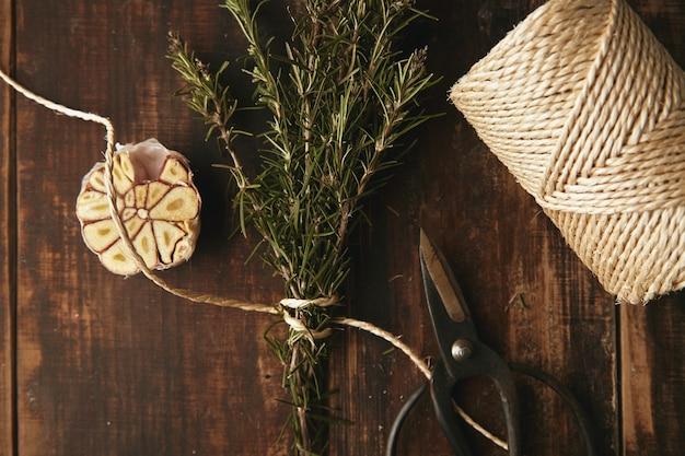 Oude tuin schaar, dik touw, knoflook en rozemarijn op grunge houten tafel. bovenaanzicht.