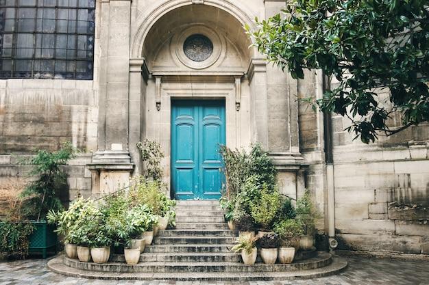 Oude turquoise deur met trappen en bloempotten