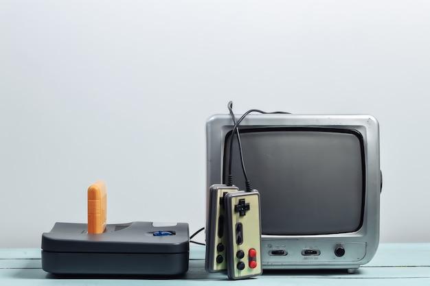 Oude tv-ontvanger met retro gameconsole, joysticks op een witte muur. retro gamen