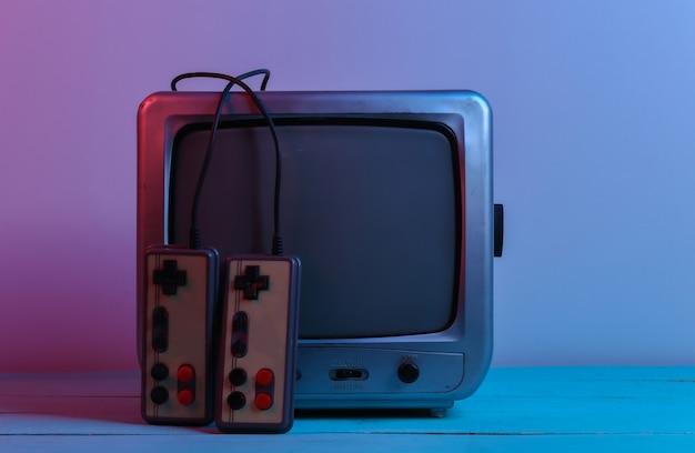 Oude tv-ontvanger met retro joysticks in rood blauw neonlicht. retro gamen
