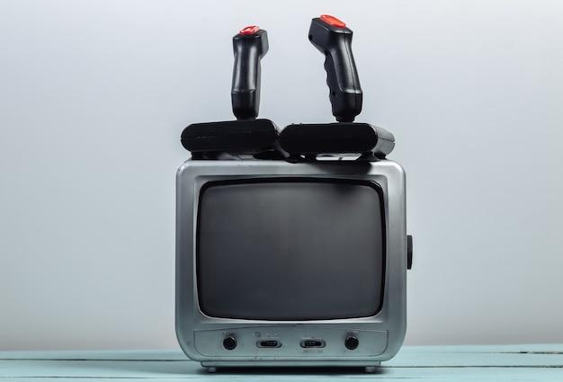 Oude tv-ontvanger met retro joysticks op een witte muur. retro gamen