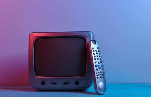 Oude tv-ontvanger met tv-afstandsbediening in rood blauw neonlicht. retro golf, media