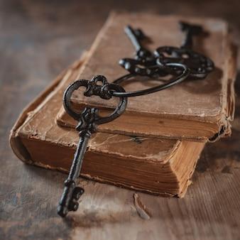 Oude uitstekende sleutels op een oud gehavend houten boek ,.