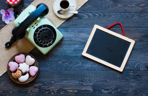 Oude uitstekende telefoon met biscottikoffie donuts op een houten achtergrond