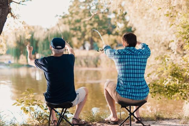 Oude vader met bebaarde zoon vissen op de rivier.